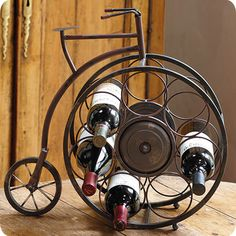 "Fun way to display your Wine! Exploring wine country by bicycle is so much more flavorful.This vintage-style high-wheeler holds seven bottles in its spokes for handsome storage in your kitchen or bar. Made of metal with a glazed rust finish. Holds wine bottles up to 31/4"" diam. Imported. 19½ x 6½ x 18¾"" h."