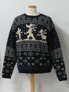 90s -Disney Store- Mens navy blue and off white snowflake background print with silhouettes of Mickey Mouse, Goofy and Donald Duck skiing on the front of this cute, longsleeve, pullover wool wicked 90s ski sweater with round neckline.