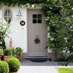 warm white house paint with taupe front door, zince farm house style light sconce, pavers, boxwoods, italian clay pots, charming cottage
