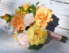 Orange and peach roses with yellow peonies mixed in.  Silk wedding bouquet by Holly's Wedding Flowers.