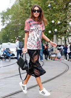 Street Style de Milão Fashion Week com look onde mulher pula vestindo saia e camiseta de paetês, bolsa croco e tenis adidas superstar