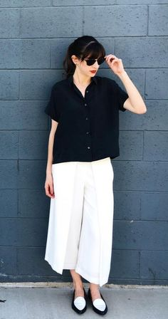 White culottes paired with a black blouse and oxfords.
