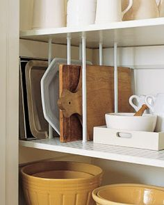 From Martha- save cabinet space in the kitchen, hang a tension rod and use S hooks to hang pots and pans. Then a magazine rack attached to the door will hold lids in place.  Also, tension rods turned vertical will sort cookie sheets and pans so you don't have to move a bunch of stuff to get the pan you want.