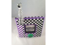 """Hand Painted 3""""x3"""" Photo Frame with 3D Attachments, Striped Animal  Acrylic paint with polycrylic finish  Frame dimensions: 9""""x9"""" excluding stand. Height with animal: 13.5""""  Holds one 3""""x3"""" photo  Original, one of a kind piece  $50.00"""