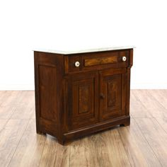 This rustic antique washstand is featured in a solid wood with a distressed dark cherry stained finish. This server bar cabinet has a white marble table top, 1 drawer and an interior cabinet with shelving. Great as a small buffet for storing dishes! #americantraditional #storage #cabinet #sandiegovintage #vintagefurniture