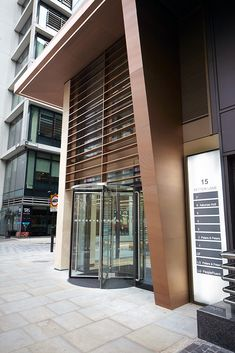 15 Fetter Lane, EC4A, London. - PVD stainless steel brise soleil, canopy and column. - Showing the relocated entrance on Fetter Lane. By John Desmond Ltd