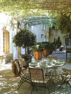 beautiful covered dining space with vines and anduze pots - so welcoming.