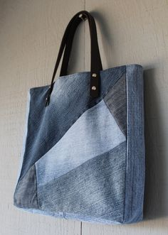 This is a handmade denim upcycled tote bag lined with a blue canvas fabric with two interior pockets. This tote has two leather straps with two rivets on each side for secure handles.  Dimensions: 11 (W) x 121/4 (H) x 2 1/2 (D) The straps are 22 Long with a 7 drop  Please feel free to contact me for custom orders.  Thank you.