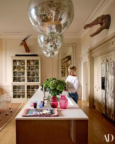 Brooke arranges hydrangeas on the Boffi kitchen island beneath disco balls. A model of the Titanic sits atop the cabinet; Florence Broadhurst wallpaper covers the refrigerator doors. Architectural Digest, Turbulence Deco, Boffi, English Manor, English Countryside, Georgian Homes, Interior Decorating, Interior Design, Decorating Ideas