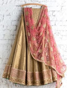 Buy this net golden lehenga choli with conscientious embroidery & lace work.This set is features a golden color blouse in silk fully embellished with foil booty work.It has matching golden lehenga in net with beautiful embroidery all over and pink dup Gold Lehenga, Indian Lehenga, Lehenga Choli, Bridal Lehenga, Sharara, Khada Dupatta, Net Lehenga, Patiala Salwar, Sabyasachi