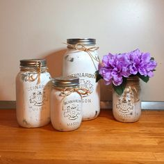 """This french white 4 piece painted mason jar kitchen gift set, complete with flower vase, adds the perfect rustic charm to your kitchen. Our unique colours add a gorgeous pop of colour to your home and pull their weight when organizing your kitchen items. The lids are covered in a beautiful jute/burlap fabric.     PLUS: Is this a gift? Are you short on time? Choose to receive the set pre-gift wrapped FOR FREE! Just select """"gift wrapped"""" in the packaged drop down menu. No other mason jar…"""