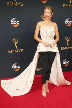 Sarah Hyland wearing a Monique Lhuillier Resort 16 cream faille floral-embroidered peplum bodice with floor-length train and black matte crêpe pants at the 2016 Emmy Awards.