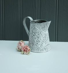 A sweet rustic shabby chic tin jug with embossed pattern.Perfect to fill with fresh or dried flowers. It has been sealed on the inside so that it can hold water. The jug is decorated with an attractive embossed design and a plain tin handle. Perfect to use to decorate your table at home or even for a wedding. Simple but attractive!    Made from tin with a matt painted finish. Should be handwashed with a mild soap.Measures 12cm in height & 6.5 cm in diameter.