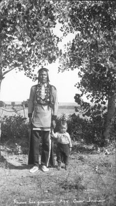 Knows the Ground with his adopted son Joe Crow (son of Eva Gun). Knows the Ground is wearing a beaded floral collar, beaded neck tie, beaded trousers, and beaded moccasins. The boy is wearing a beaded leather coat, cotton pants and contemporary shoes. Date: 1917-1928. William Wildschut photograph collection; National Museum of the American Indian Archive Center, Smithsonian Institution.