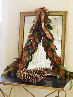 """Dress up a mirror or mantel with a graceful magnolia garland. Cut floral wire to desired length (4 feet). Fan out three to five leaves on a flat surface and twist floral wire around stems. Keep working down the wire, adding three or more leaves at a time, twisting stems together with wire as you go. Vary the pattern by turning random leaves to reveal bronze underside, make an """"S"""" hook with floral wire at center of mirror. Hang garland so both sides drape naturally. Secure a bow with floral…"""