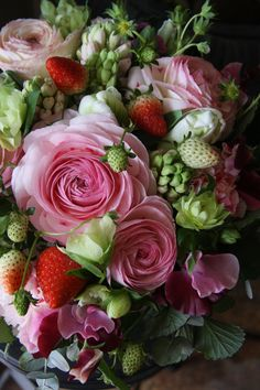 Roses and wild strawberries floral arrangement for a summer table
