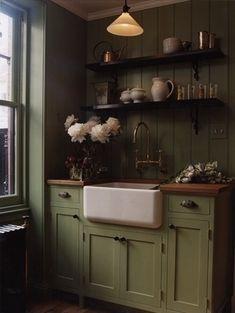 Flower Room with olive green cabinets & backsplash with black open shelves