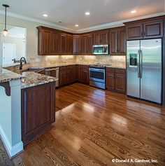 A spacious #kitchen finished with hardwood floors and a neutral backsplash. The Whitford #1298-D. http://www.dongardner.com/house-plan/1298-D/the-whitford. #OpenConcept #DreamHouse