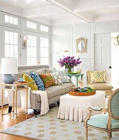 This living room is both colorful and soothing because the largest surfaces are in soft colors- white, gray, beige, aqua and the blue and beige of the rug.  The Vibrant Colors are all in the Pillows...