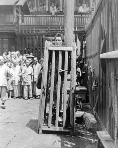 A man convicted of murder is imprisoned in a wooden cage on a street in China. He will be left to die of thirst,starvation and exposure.  Circa 1930