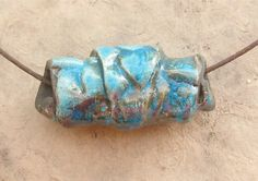 Raku Ceramic Bead - Large Turquoise Leaf Croissant Bead This bead is made of raku-fired porcelain and features an unusual rolled-up structure and an impressed design of small leaves. The bright turquoise glaze features a fine crackle pattern and speckles of metallic copper. The listed price is for one bead but I do have three of these beads available. The bead is 20 mm wide at the widest, 46 mm long and has a 6.5 mm hole through the center. The cord in the photos is there just to show ...