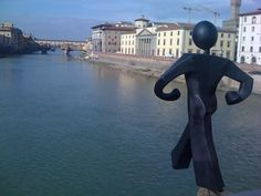 Abraham Clet's statue on the Arno River in Florence