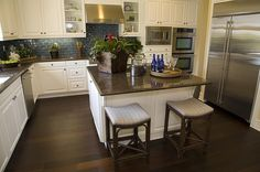 This is warm for being a white cabinet kitchen... Stools on opposite side of counter. Blue glass tile backsplash