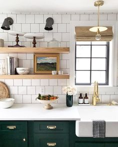 white tile, open shelving, farmhouse sink, and dark green lower cabinets. AMAZING kitchen
