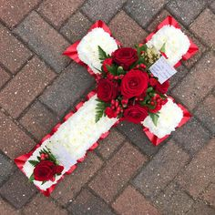 A striking white based cross with red ribbon edge and red rose focal spray, a beautiful alternative to a traditional floral coffin spray or sympathy flower wreath Diy Sympathy Flower Arrangements, Funeral Floral Arrangements, Sympathy Flowers, Flower Wreath Funeral, Funeral Flowers, Cemetery Flowers, Grave Flowers, Casket Flowers, White Rose Flower