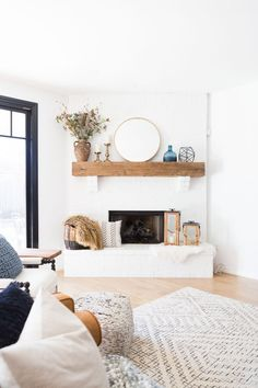 Home Decorating DIY Projects : White Painted Brick Fireplace Makeover TV collage wall pottery barn wood media console article sven leather sofa faux fiddle leaf fig tree wood lanterns round gold mirror fireplace styling white walls black windows -Read More –