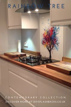This abstract Rainbow Tree glass splashback adds colour to a simple scheme. It works beautifully with the wooden worktop and sleek handleless units. For more kitchen ideas visit Wooden Worktop Kitchen, Handleless Kitchen, Glass Kitchen, Kitchen Colors, Kitchen Backsplash, Kitchen Splashback Ideas, Open Kitchen, Kitchen Layout, Design Kitchen