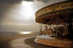 Carousel on Brighton Beach. This image may be responsible for my semi-recent casual interest in vintage carousels. Kudos, oh moody British seaside fun.