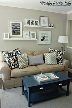 arrangement of ledges and photos above couch