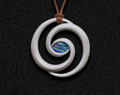 BONE NECKLACE: The Eye of Ngā Atua (The Eye of The Gods) The spiral is the oldest known symbol of human spirituality. Based on the double spiral found on the bow of the Maori Chiefs War Canoe (see image), and in the shape of a new unfurling silver fern frond, this pendant symbolizes 'Mauri', life