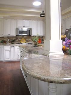 Cream cabinets, stainless steel appliances, and solar tube skylight ~ light & reflective kitchen