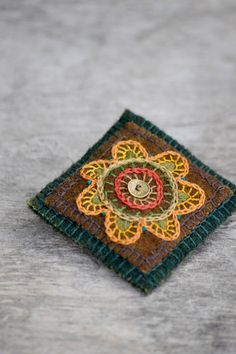 Natural floral brooch. Hand-stiched woolen brooch with floral embroidery. Folk and ethnic brooch.
