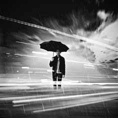 This photo has a man standing with an umbrella in it, he is still in focus but the motion behind him is blurred as it isn't the main part of the image.