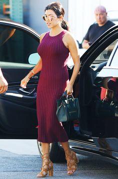 Kourtney Kardashian wears a ribbed tank dress, lace-up sandals, mirrored sunglasses, and a Céline mini tote bag