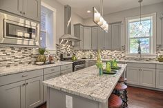 White and gray random tile backsplash with hardwood throughout kitchen. Floors And More, Backsplash, Cleveland, Hardwood, Tile, Flooring, Gray, Random, Kitchen