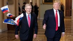 """A protester throws Russian flags at Senate Majority Leader Mitch McConnell and President Donald Trump as the latter arrives on Capitol Hill for meetings with senators on Tuesday. The protester, who identified himself as Ryan Clayton with the group America Take Action, threw the flags before being escorted out of the Ohio Clock corridor. The flags had the word """"Trump"""" on them."""