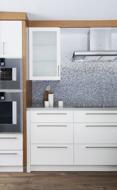 The home abuts a river, where the residents enjoy kayaking and swimming in warmer months.  This geographic blessing partially inspired the wave-like backsplash. Each tile was hand-cut and individually placed by artisans from New Ravenna.