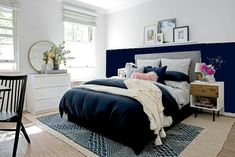 Deep blue bedroom wall with picture rail and grey cushioned headboard