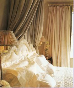 Isn't this warm and welcoming. Love the striped bed draperies and the voluminous window draperies.
