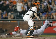 Cincinnati Reds first baseman Joey Votto scores past San Francisco Giants catcher Buster Posey (R) on a fourth inning single by Cincinnati Reds Scott Rolen during Game 2 of their MLB NLDS playoff baseball series in San Francisco, California October 7, 2012. (REUTERS)