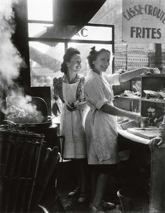 The war is over! Post World War II, a couple of French gals take part in the small pleasures of life in Willy Ronis' 1946 silver print entitled Rue Rambuteau.