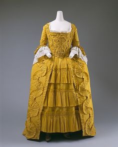 Bright yellow silk robe à la française with white linen and cotton ruffles, British, ca. 1760. Monochrome, but in a bright canary yellow guaranteed to catch anyone's attention across a room, this exceptionally well-preserved gown with trimmings represents the apogee of the form. The absence of ornament, other than basic ruffles, makes this a perfect example, free from distractions and affirming thereby the adorned beauty of 18th C. silhouette and style, so often masked under frills and coquetry.