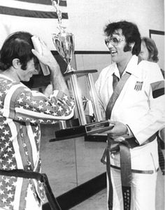 Elvis is presenting Bill Wallace with a trophy for his promotion to a 4th Black Belt at the TKI, 1974. Elvis was the Grandmaster.