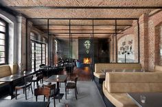 The brick in the less formal areas retains its original color offering a more rustic feel. The architects used a series of open metal frames which set up a spatial rhythm, demarcating zones while preserving transparency.