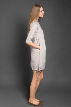 Light grey linen dress with 3/4 sleeves, with two pockets on sides and a drawstring decoration at the bottom. The dress is fastened with a line of buttons at the back. Perfect for hot summer weather. You can wear this dress at work, on a beach, on special occasion or casual. It also helps to hide undesired features like a rounder stomach or larger hips.  Composition: 100 % linen. Shrink-resistant fabric due to a special wash in the manufacturing process. Measurements: perfect for high 16...
