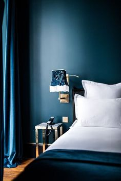 Sophisticated dark blue bedroom from a hotel in Paris | crisp white bedding, dark blue bedspread and blue curtains | art deco wall sconce with a tasseled lampshade | Get the look with a velvet bedspread from Bemz